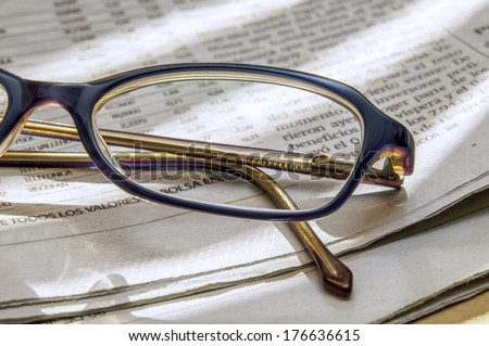 newspaper full of interesting news and reading glasses - stock photo