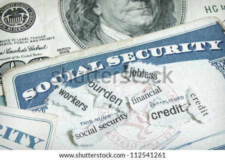 newspaper headlines and social security cards with cash - stock photo