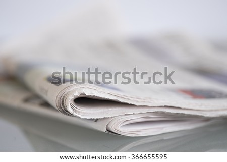 Newspaper mirrored on glass table with shallow depth of field - stock photo