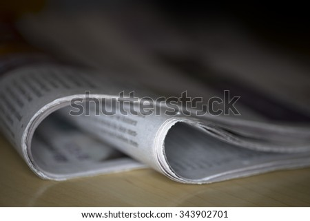 Newspaper on a wooden table, against black background with shallow depth of field - stock photo
