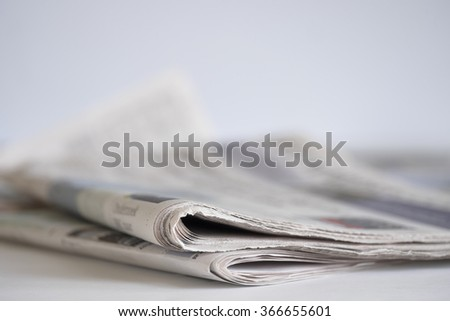 Newspaper on white table with shallow depth of field - stock photo