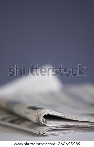 Newspaper on white table with shallow depth of field against dark blue background - stock photo