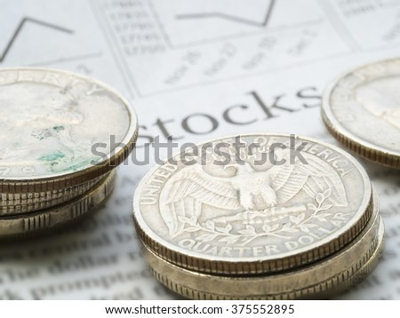 "Newspaper open to stock market page showing word ""Stocks"" and coins. Concept of Investment."