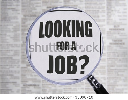 Newspaper opend to the want ads. Magnifying glass highlighting the word Jobs. - stock photo