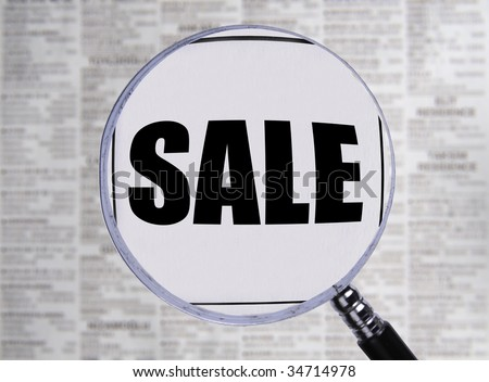 Newspaper opened to the want ads. Magnifying glass highlighting the word sale. - stock photo