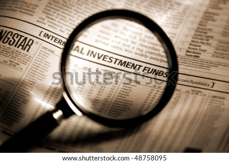 Newspaper section of the stock market index through the magnifying glass. Shallow depth of field - stock photo