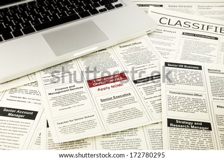 newspaper with advertisements and classifieds ads for vacancy, job search and apply now - stock photo