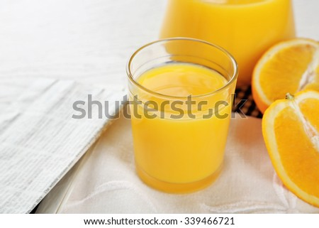 Newspaper with oranges and juice on blue checkered napkin, close up