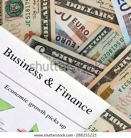 Newspaper with the headline Business and Finance. World currency in the background. - stock photo
