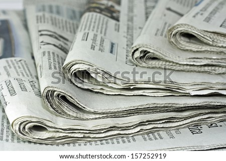 newspapers against plain background shot with very shallow depth of field - stock photo