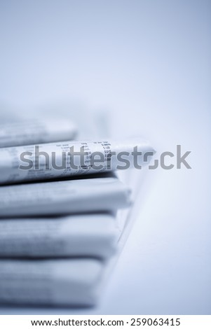 newspapers against plain background shot with very shallow depth of field - Blue tone - stock photo
