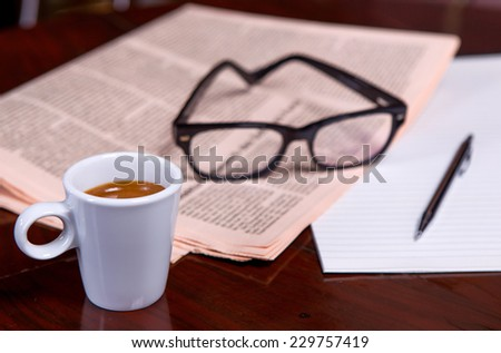 Newspapers and coffee cup, reading glasses, pen and striped paper.
