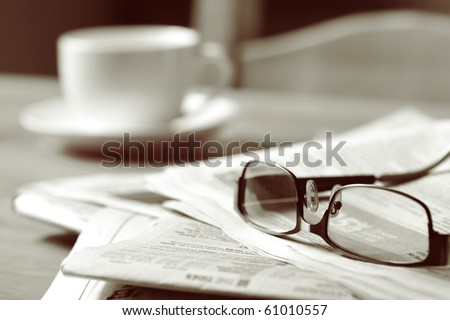 Newspapers and coffee cup, with reading glasses.  Toned image, focus on reading glasses. - stock photo