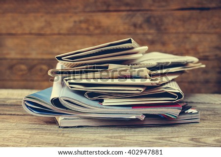 Newspapers and magazines on old wood background. Toned image - stock photo