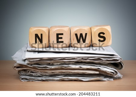 Newspapers folded and stacked with the word news in wooden block puzzle dice concept for newspaper, the media, press release and global communications - stock photo