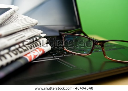 Newspapers laptop glasses in composition on green background