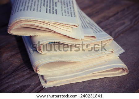 Newspapers on old wood background. Toned image.  - stock photo