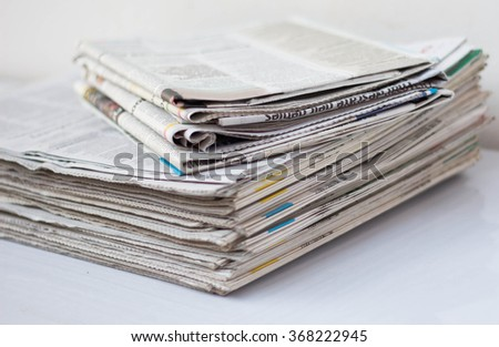 Newspapers on white table.