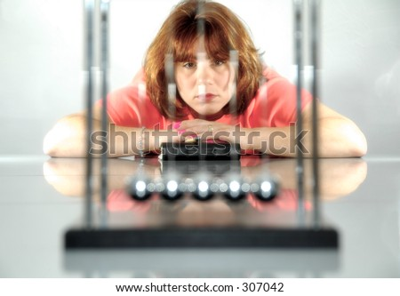 Newtons Balls in Foreground out of Focus WIth Woman in Background in Focus. - stock photo