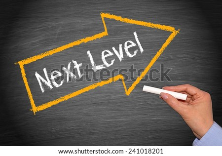 Next Level - female hand with chalk and arrow on blackboard background - stock photo