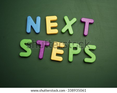 next steps concept in colorful letters isolated on blank blackboard