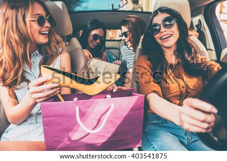 Next stop is lingerie shop! Four beautiful young cheerful women holding shopping bags and looking at each other with smile while sitting in car - stock photo