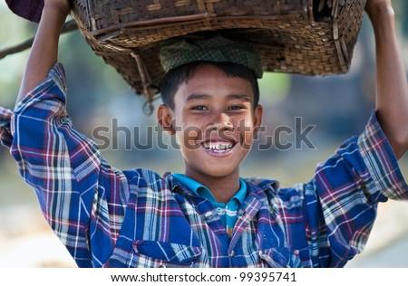 NGAPALI, BURMA - JANUARY 21: Smiling boy Thin Moe, 11 with basket posing for the photo during the Hta-Mane Festival on January 21, 2011 in Ngapali, Burma - stock photo