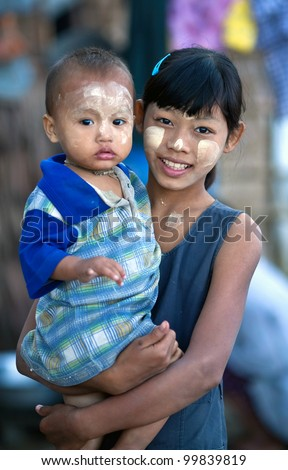 NGAPALI, MYANMAR - JANUARY 21: Smiling girl Soe Soe, 11 and her little unidentified sister with thanaka paste on the face posing for the photo during the Hta-Mane Festival on January 21, 2011 in Ngapali, Myanmar - stock photo