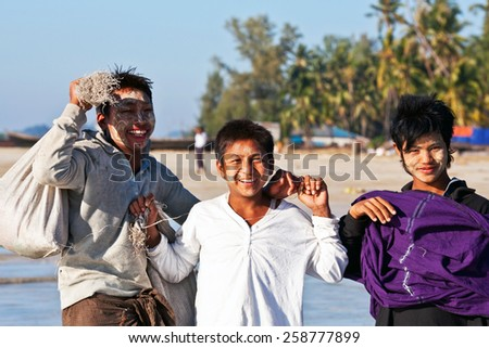 NGAPALI, RAKHAIN STATE, BURMA - JANUARY 23: Young smiling fishermen with thanaka paste on their faces poses for a photo during the Hta-Mane Festival on January 23, 2011 in Ngapali, Burma - stock photo