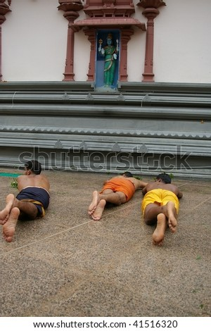 NGAPORE, SINGAPORE - NOVEMBER 04: Hindus doing ritual rolling (Angapirathatchanam) at Sri Mariamman Temple for the Thimithi Festival  November 04, 2009 in Ngapore, Singapore. - stock photo