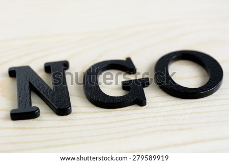 NGO letters on wood background - NGO stand for Non-Governmental Organization - stock photo
