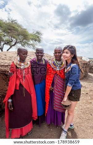 NGORONGORO,  TANZANIA- DECEMBER 29, 2013: Tourist enjoys taking pictures with Masai women - stock photo