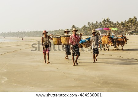 NGWE SAUNG, MYANMAR - MARCH 23, 2015. Burmese fishermen bear caught fish in baskets on the beach Ngwe Saung Myanmar