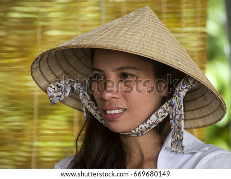 NHA TRANG, VIETNAM – DECEMBER 2012: Young Vietnamese woman with the traditional conical hat.