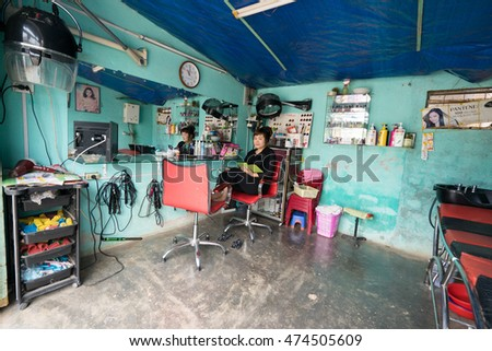NHA TRANG, VIETNAM - JUNE 23, 2016: Empty beauty shop in Vietnam. The hairdresser is sitting in a chair.
