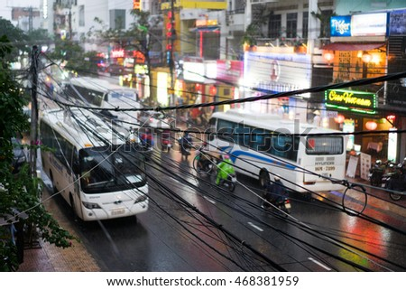 NHA TRANG, VIETNAM - JUNE 20, 2016: Evening view of the downtown with illuminated signs on the shops and busses, motorbikes and bycicles on the traffic road at rainy weather