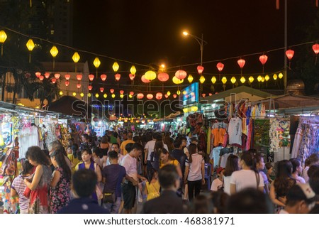 NHA TRANG, VIETNAM - JUNE 19, 2016: People are walking on the night illuminated market street in the touristic zone in Vietnam