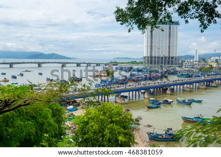 NHA TRANG, VIETNAM - JUNE 21, 2016: View of the bridge through the river with a set of fishing and transport boats. The high building and mountains in the distance