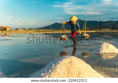 Nha Trang, Vietnam. Women carry salt from salt farm to factory. - stock photo