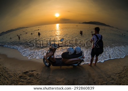 NHATRANG, VIETNAM - JUNE 25 : Young man stands near a new Yamaha scooter on the beach at June 25, 2015 in Nhatrang, Vietnam