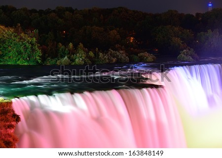 Niagara Falls lit at night by colorful lights - stock photo