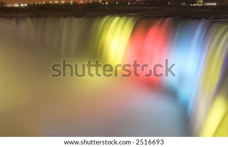Niagara Falls lit up at night with a wonderful array of colors - stock photo