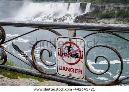 NIAGARA FALLS - MAY 29: Danger sign near Niagara waterfall seen on Canadian side in Niagara Falls on May 29, 2016 in Niagara Falls, Canada. - stock photo