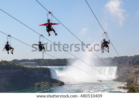 NIAGARA FALLS, ONTARIO, CANADA - SEPTEMBER 4: Four people taking zipline ride at Niagara Falls in summer on Sep. 4, 2016, Ontario, Canada.  New zipline in Niagara Parks opened in the summer of 2016