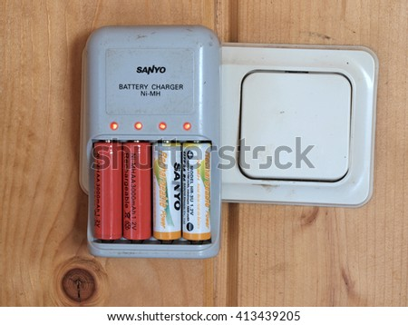 NICA, LATVIA - APRIL 30, 2016: Rechargeable Ni-Mh AA batteries are charging by charger from wall socket.        - stock photo