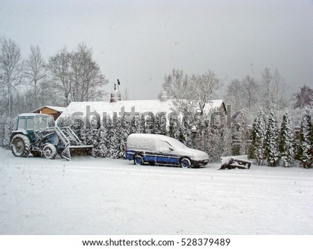 NICA, LATVIA - DECEMBER 3, 2016: In country farm yard after snowfall tractor and car are covered with snow.