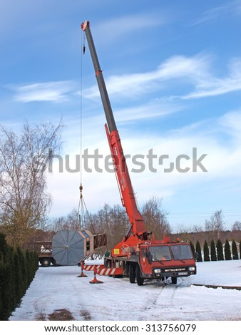 NICA, LATVIA - FEBRUARY 20, 2013: Heavy mobile crane are lifting up metal tower parts for loading to truck trailer on snowy winter sunset time. - stock photo