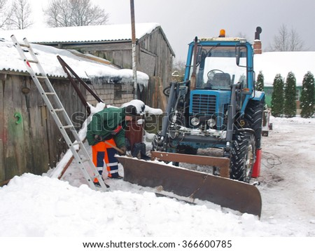 NICA, LATVIA - JANUARY 24, 2016: Country farmer is removing snow around the tractor.   - stock photo