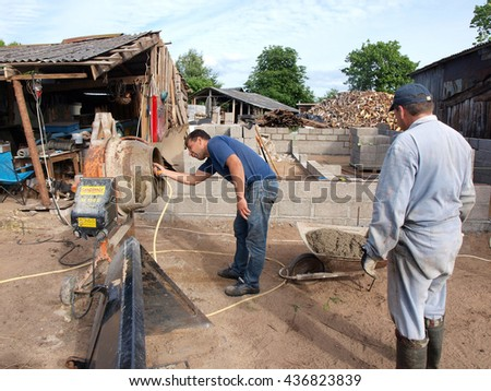NICA, LATVIA - JUNE 13, 2016: Construction worker with watering hose is washing cement mixer.       - stock photo