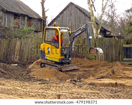 NICA, LATVIA - MARCH 21, 2009: Young man worker with yellow mini excavator is building grovel road in country farm yard.